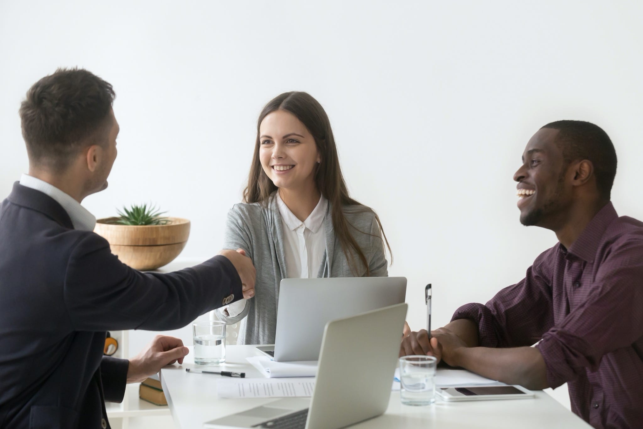 negocieri - Smiling businesswoman shaking hand of male partner at group meeting