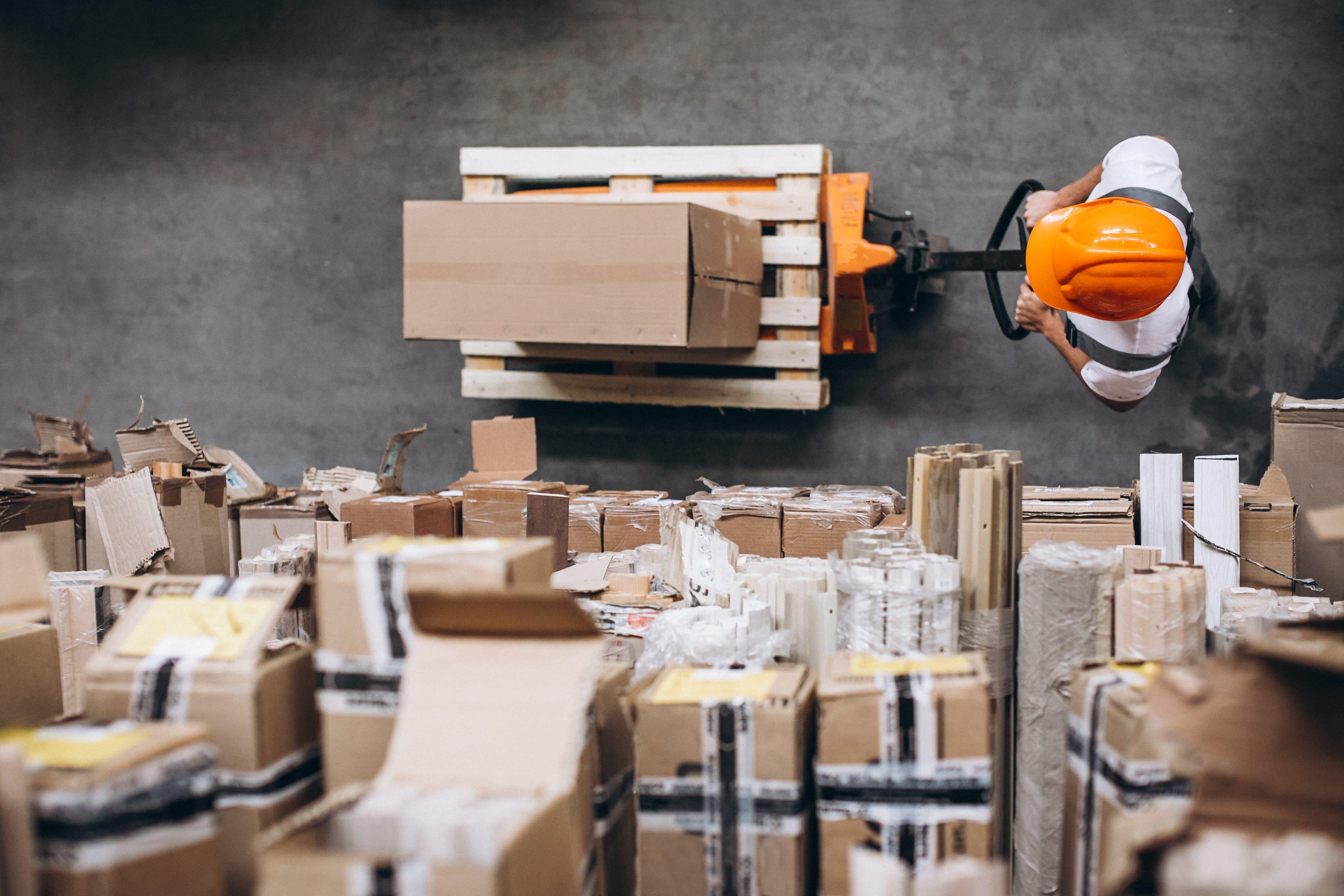 young man working warehouse with boxes - Piața spațiilor industriale și logistice din România, în competiția dezvoltării cu marii campioni regionali